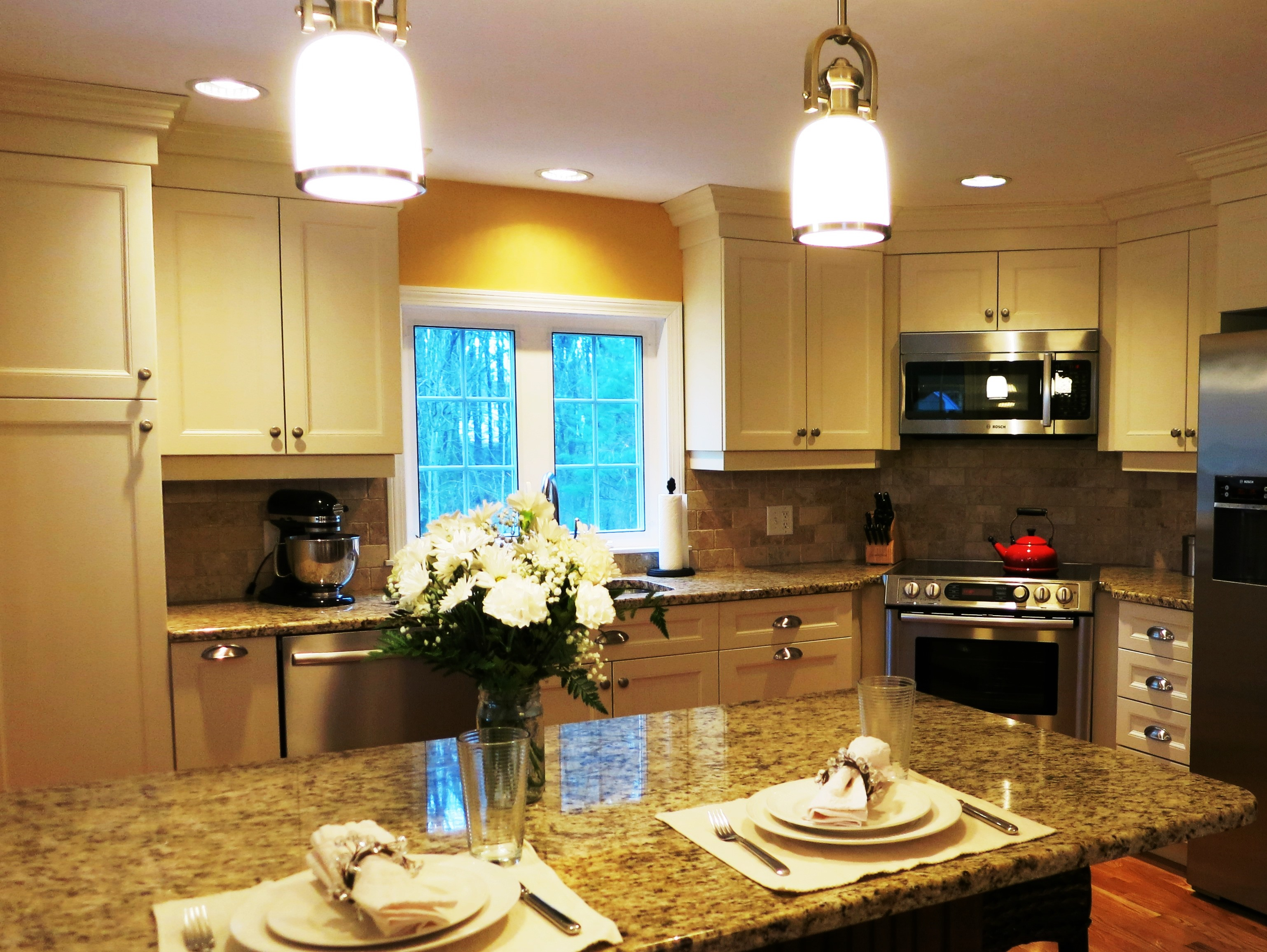 Transitional kitchen with off white thermofoil door and stained maple penninsula